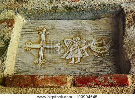 The cross, the angel and a bird in the wall of ancient monastery in Greece