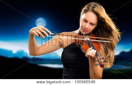 Blonde violinist playing the violin in the moonlight