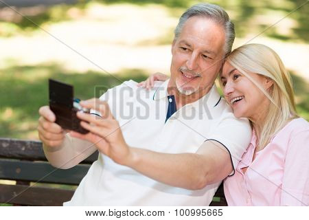 Portrait of a mature couple taking a self portrait in a park