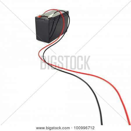 Battery with cables. Industrial battery hooked up with long red and black cables coming from the terminal. Isolated on white.