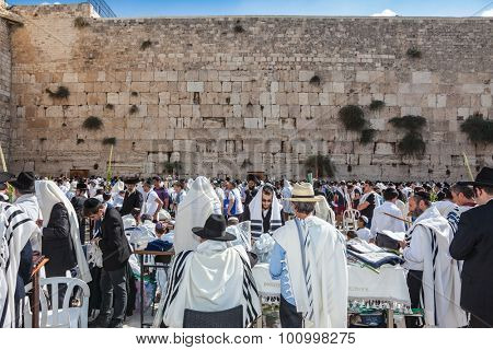 JERUSALEM, ISRAEL - OCTOBER 12, 2014:  Hhuge crowd of faithful Jews wearing white prayer shawls and black long-skirted coats. Morning autumn Sukkot