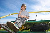 stock photo of bleachers  - Young teen aged boy talking on cell phone sitting on bleachers with a laptop beside him - JPG