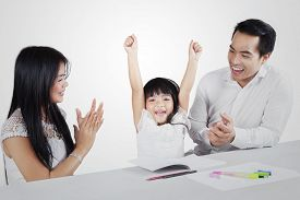 picture of applause  - Portrait of a cute girl expressing happy after finishing her homework with her parents and get applause isolated on white background - JPG