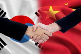 picture of politician  - Two politicians shaking hands after good deal in front of the chinese and south korean flags - JPG