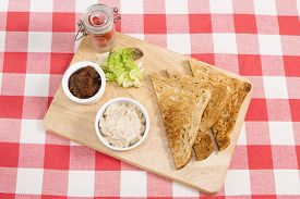 stock photo of canard  - a pot of creamy salmon pate on a wooden board with pickle and triangles of toast - JPG