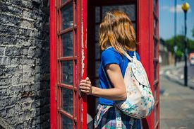 picture of phone-booth  - A young woman is entering a traditional red english phone booth on a sunny day  - JPG