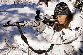 image of sniper  - Sniper girl in white camouflage aiming with rifle at winter forest - JPG