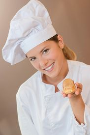 image of eclairs  - Female baker holding an eclair - JPG