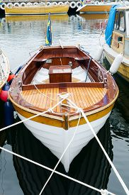 stock photo of sloop  - old beutiful open boat with motor and flag and shining - JPG