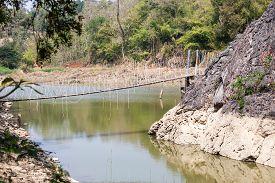 foto of suspension  - above the water between two rocks hangs a suspension bridge - JPG