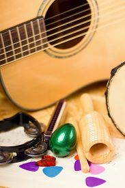 pic of bongo  - Vertical photo of several musical instruments as green egg shaker guiro harmonica bongo and acoustic guitar with few color picks - JPG