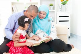 stock photo of malay  - Malay family reading in the living room - JPG