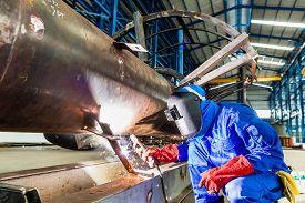 image of pipe-welding  - Welder in factory welding metal pipes - JPG
