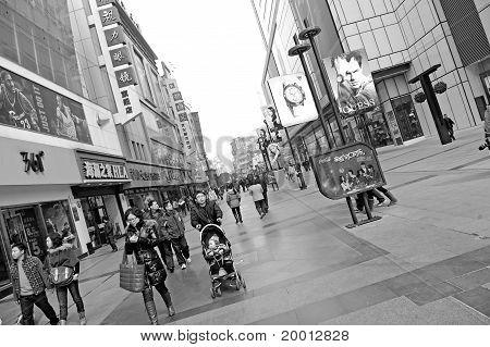 People pass through a busy pedestrian shopping street