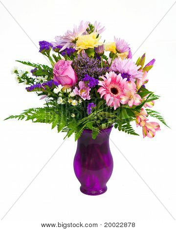 Colorful flower bouquet centerpiece in vase isolated on white.