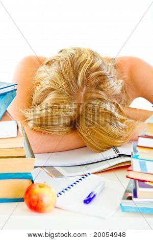 Tired young girl sleeping at table with piles of books