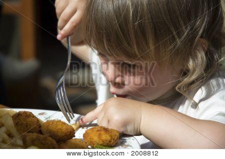 Pequeña niña comiendo papas fritas