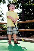 pic of miniature golf  - Young boy plays mini golf on putt putt course - JPG