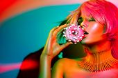 High Fashion model woman posing in studio with donut in colorful bright lights, portrait of stylish  poster
