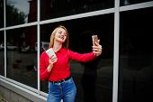 Portrait Of A Beautiful Woman In Red Blouse And Casual Jeans Taking Selfie On Mobile Phone And Holdi poster