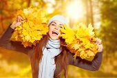 Beautiful Happy Autumn girl holding bunches of bright yellow autumn leaves and laughing. Beauty fall poster
