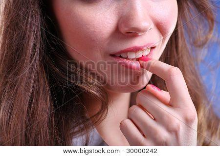 脸上一个漂亮的年轻女人碰触到的嘴唇