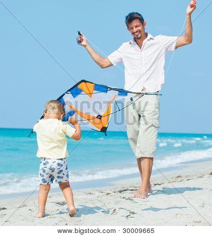niño con el padre en la playa jugando con una cometa