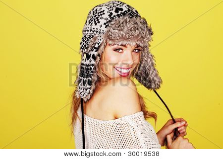 Vivacious happy young woman in a woolly winter hat with earflaps looking over her shoulder at the camera.