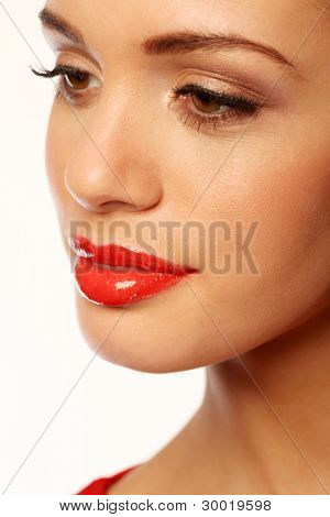 Closeup of a beautiful woman with luscious full glossy red lips.