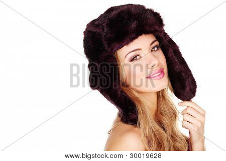 Pretty smiling young girl in a furry winter hat with earflaps facing out of frame with copyspace behind