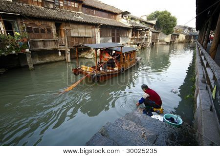 WUZHEN, CHINA - NOVEMBER 25: Tourists in a paddle boat watch a local lady wash her clothes the traditional way in the river in this 1300 years old water town on November 25, 2011 in Wuzhen, China.