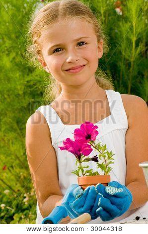 Gardening, planting - Lovely gardener girl planting flowers into the flowerpot