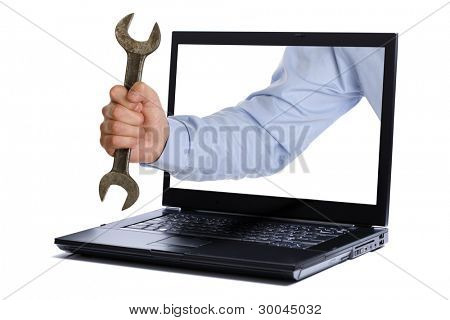 Hand holding spanner through the screen of laptop
