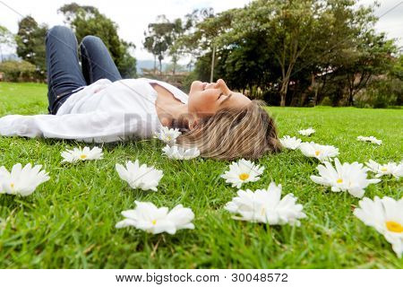 Beautiful casual woman relaxing outdoors lying on the grass