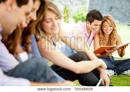Happy group of young student sitting outdoors