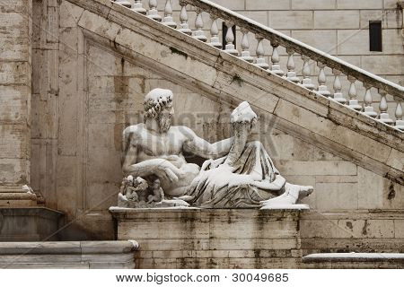 Statues in Campidoglio square under snow