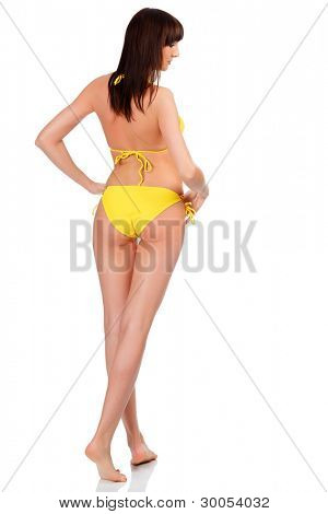 Sexy woman wearing yellow swimsuit posing against a white background.