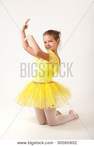 Cute little ballerina exercising, studio shot on white background
