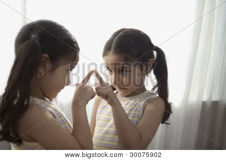 Girl looking at herself in mirror