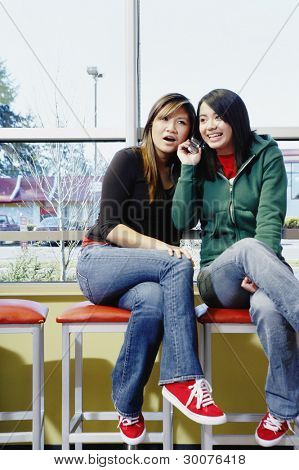 Two teenage girls talking on cell phone