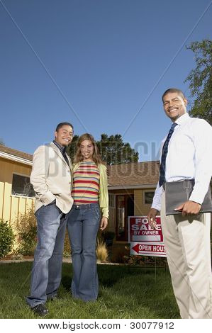 Portrait of couple with realtor at open house