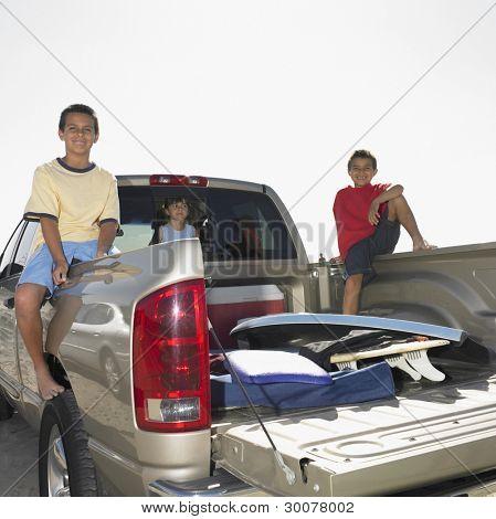 Portrait of siblings in back of truck