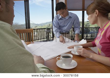 Man showing house plans to couple