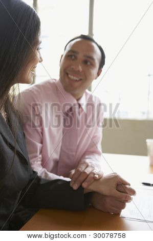 Couple holding hands at desk