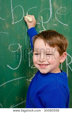Young boy writing on chalk board