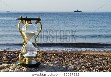 Bronze hourglass on a beach