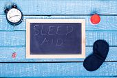 Sleep Concept Showing An Alarm Clock, Sleeping Pills, An  Eye Mask And A Black Board Reading Sleep A poster
