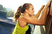 stock photo of parkour  - Young woman traceur climbing an obstacle while participating in parkour - JPG