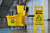 picture of janitor  - Mop bucket and caution sign inside a building - JPG