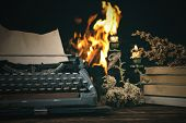 Typewriter, Stack Of Books, Burning Candle On A Writer Table On A Burning Fire Background. poster
